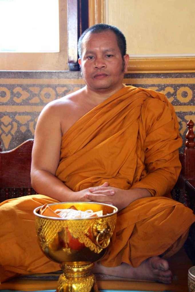 Monje recibiendo ofrendas en el templo del buda de oro, Wat Traimit, en Bangkok, Tailandia.