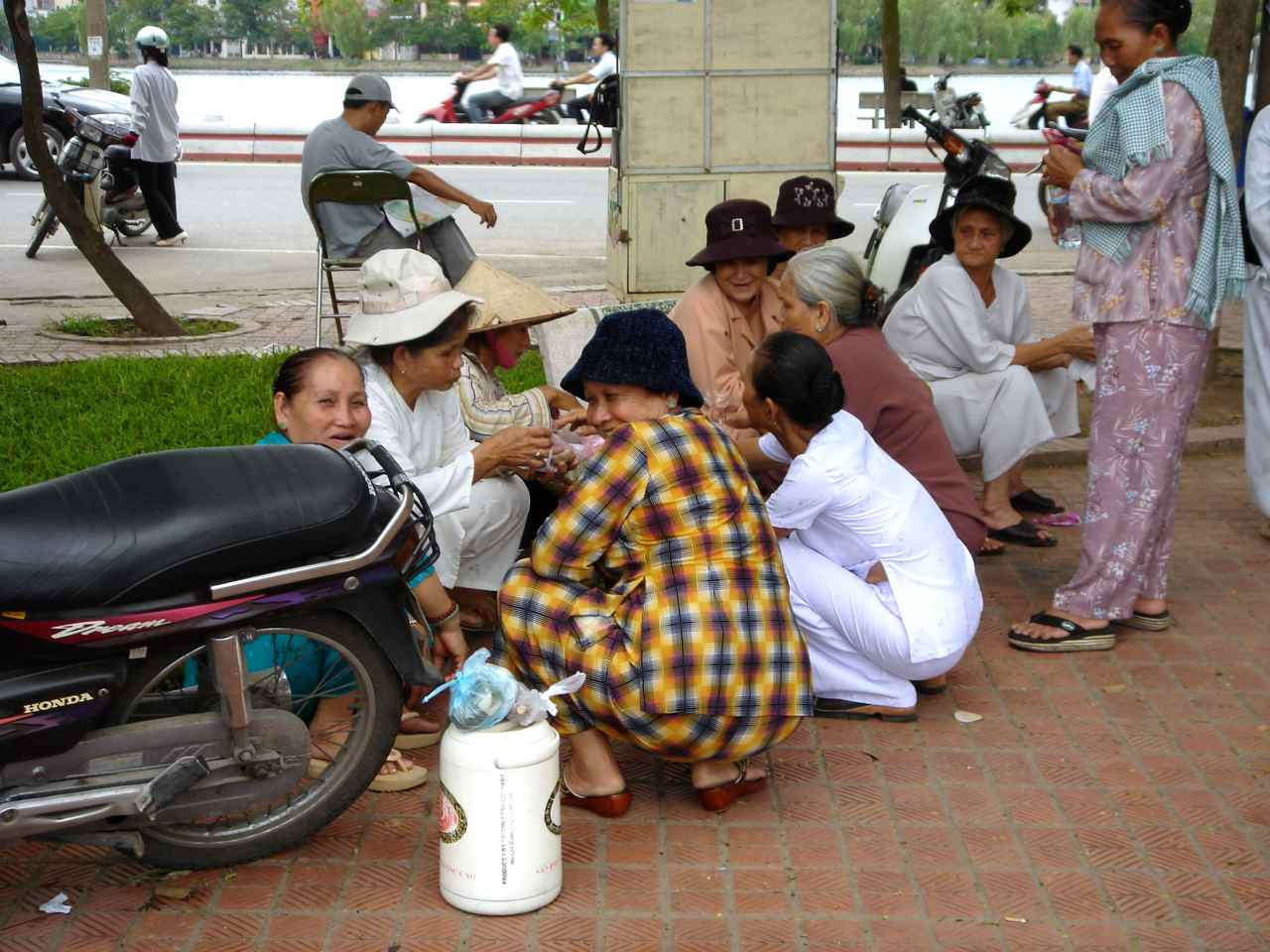 mujeres sentadas junto a La Pagoda de Tran Quoc en Hanoi (Vietnam)